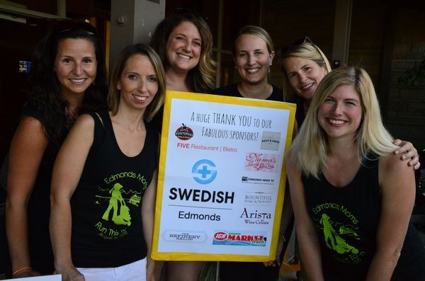 Local MOPS chapter members stand by the sign identifying the sponsors of this year's Edmonds Moms Run This Town event. L to R, Lindsay Crawford, Heidi Morris, Heather Damron, Kate Nichols, Megan Harrington and Tracy Perkins
