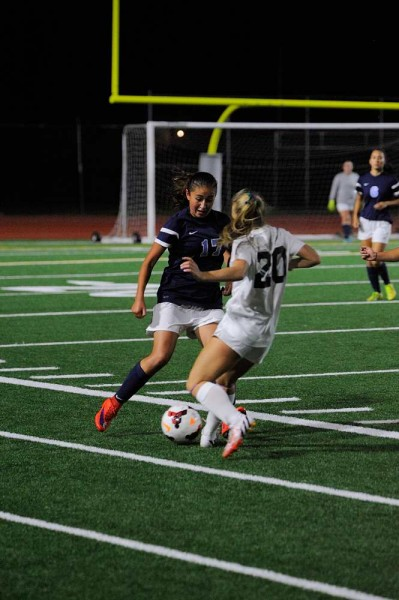 Meadowdale's Adriana Valadez (left) tries to get past Edmonds-Woodway's Savannah Norton during a Wesco 3A game against Edmonds-Woodway Wednesday night at Edmonds Stadium. The Warriors won 2-0. (Photos by Karl Swenson)