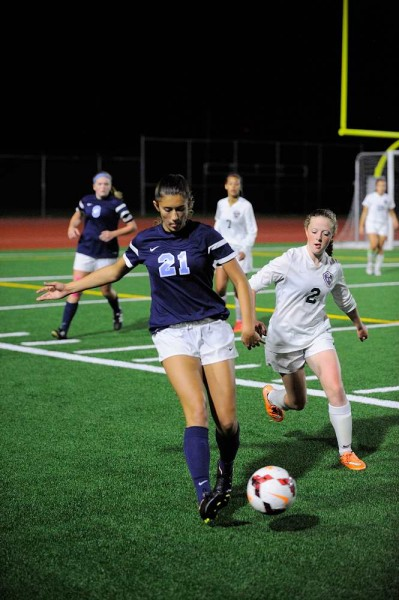 Meadowdale's Alex Hughes (left) beats Edmonds-Woodway's Molly Carden to the ball.