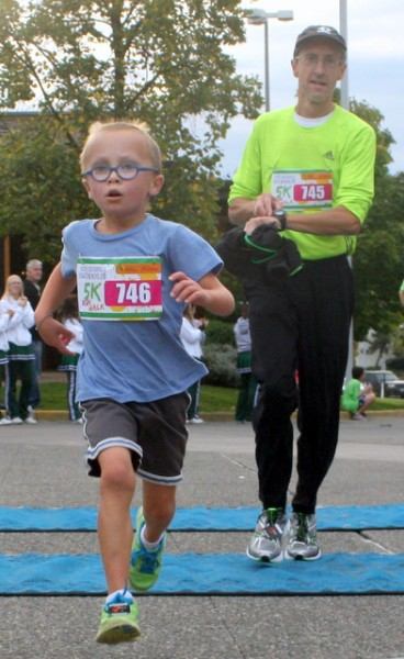 Max Billett finishes the 2014 Celebrate Schools! 5k Run/Walk ahead of father Mark. (Photo by David Pan)