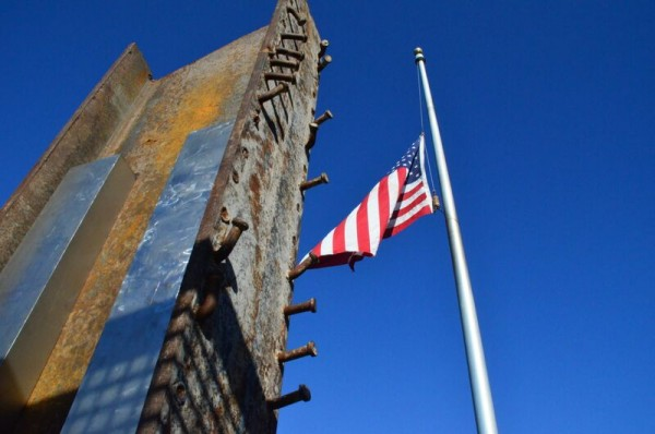 The American Flag flies at half staff in the shadow of the steel girder from the wreckage of the Twin Towers, which now stands as the centerpiece of the new Edmonds 9-11 Memorial.
