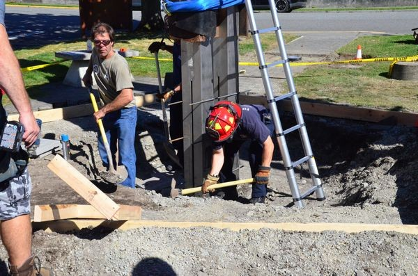 With the crane holding the beam in place, Edmonds firefighters make last-minute adjustments to the footings.