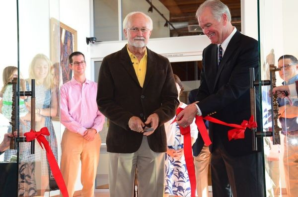 As son Nick looks on, Cascadia Art Museum founder Lindsey Echelbarger is assisted by Edmonds Mayor Dave Earling in cutting the ribbon to officially open the museum Saturday. (Photo by Larry Vogel)