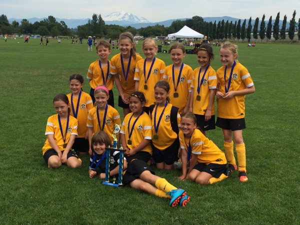 Members of the FC Edmonds Quiet Riot U10 girls soccer team pose withe their trophy after going undefeated during the second leg of the Northwest Champions league competition held last weekend at 60 Acres park in Redmond. The team scored 19 goals to 2, winning all four games, which placed them third overall in the competition. The team plays in the semifinals in March. (Photo courtesy of Joshua Cardin)