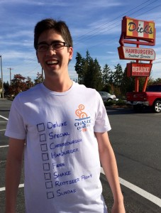 Walker Kevin Drake at the Edmonds starting line with his customized Dick's shirt, displaying a checklist of menu items that he'll consume during the walk.