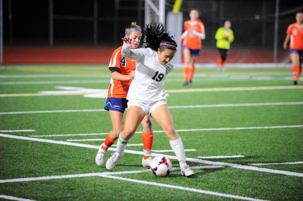 E-W's Kia Mackey battles Eastside Catholic's Sophia Cerino for ball control.