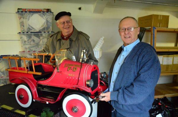 Edmonds Museum Board President Bill Lambert presents the classic pedal fire truck to Walt Poirier, this year's raffle winner.