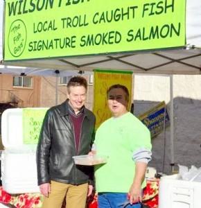 City Economic Development Director Patrick Doherty samples some of Wilson Fish Markets' custom smoked salmon.