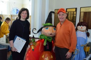 "Maggie Stokes, who took first place honors in the residential category, flanks her winning entry ""Li'l Pumpkin & Big Blood Moon"" with Dave Buelow, Scarecrow Festival Coordinator."