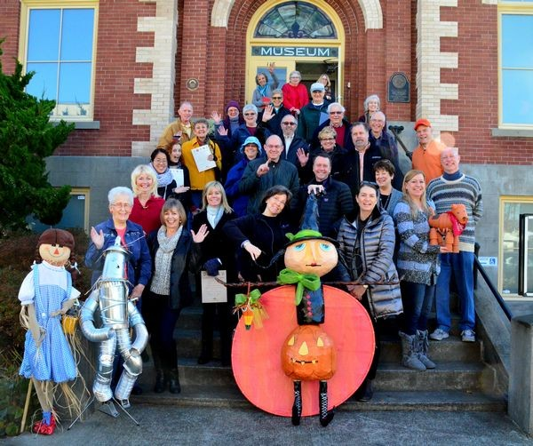 "The 2015 Scarecrow Festival Winners share the Museum steps with staff, well-wishers, and scarecrows ""Dorothy and Tin Man,"" and ""Li'l Pumpkin & Big Blood Moon."""