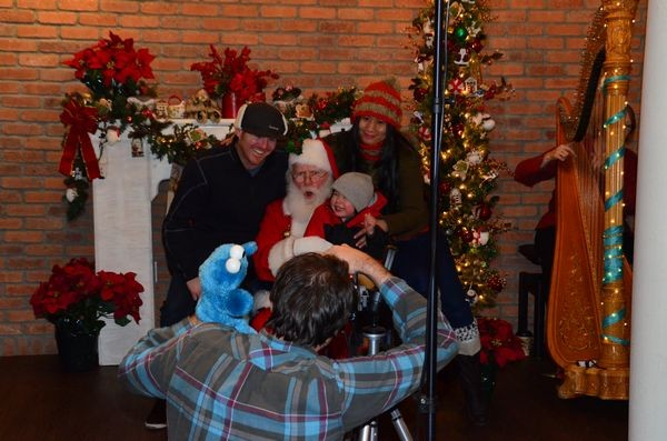 Families gather at Canarino Gelato following the tree lighting to have their picture taken with Santa. (Photo by Larry Vogel)