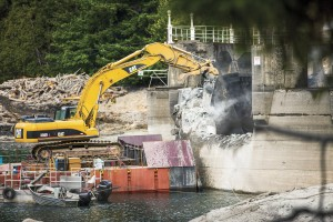 """In a scene from """"Damnation,"""" a barge-mounted excavator hammers away at Glines Canyon Dam on the Elwha River in Olympic National Park. (Photo by Ben Knight)"""