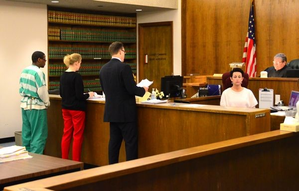 Christopher V. Cowan, standing before Judge George Bowden, listens as his defense attorney Jennifer Bartlett and prosecuting attorney Craig Matheson present final arguments in his sentencing.