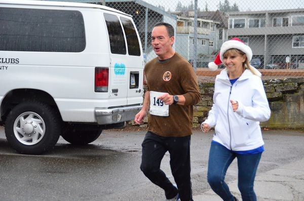 Race coordinator and Police Foundation vice president Darlene Stern joins third place finisher Dan Guerrero to run across the finish line.