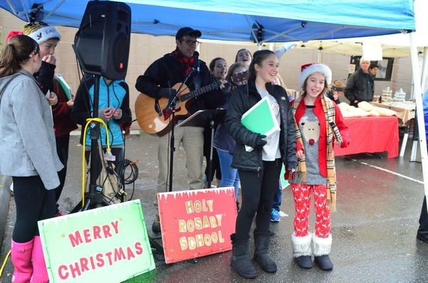 Holy Rosary 7th and 8th graders singing holiday favorites and the Edmonds Holiday market.