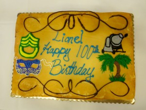 The cake designed for Lionel Duvernay's party featured the iconic highlights of his life: an Army patch for his military service, a cement mixer representing his career, a palm tree representing his South Pacific assignment during WWII, and a Mardi Gras mask celebrating his New Orleans heritage.