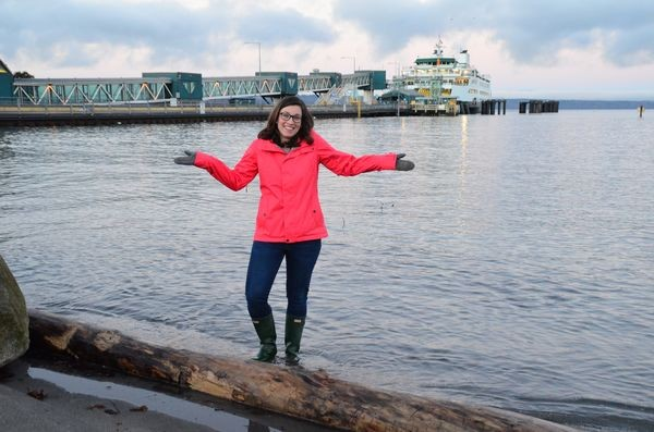 "Chelsea Kahn, Washington Sea Grant Research and Education Specialist, wades in today's King Tide waters as they lap against the Brackett's Landing seawall.  ""Today this is a very high tide, but by mid-century it will be the normal sea level,"" she explained"