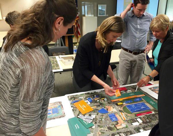 Walker Macy's Ann Marie Schneider demonstrates a planning diagram for Civic Field as meeting attendees Emily Scott