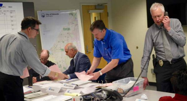Edmonds Police Chief Al Compaan, far right, takes a phone report from city public works crew during the Cascadia Rising exercise Wednesday morning. Other city staff and first responders sorting through emergency reports are, from left, City Clerk Scott Passey, Fire District 1 Battalion Chief Gary Kestle, Public Works Director Phil Williams and City Engineer Rob English.