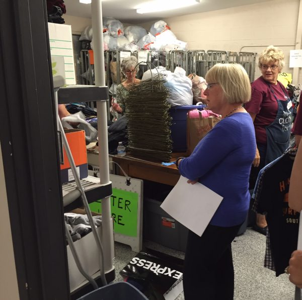 Sen. Patty Murray (D-WA) looks at shelves of clothing while volunteers continue their work in the background. (Photos courtesy Clothes for Kids)