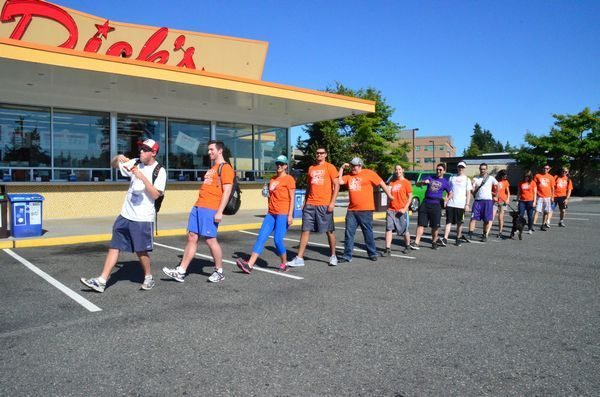 """With Walkathon co-founder Lars Phillips in the lead and striking an R. Crumb-inspired """"Keep on Truckin"""" pose, the group sets out on the 2014 Walkathon from the Edmonds Dick's heading for the next stop, the Lake City location. (Photo by Larry Vogel)"""