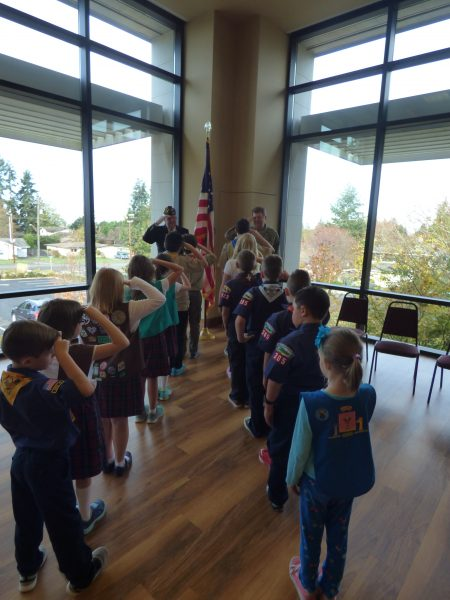 Sue Venable of the Holy Rosary students' Veterans Day assembly yesterday (Thursday). Students who are also Boy and Girl Scouts are saluting two visiting military veterans: Jim Collins, US Air Force (photo left), and Jay Schatz, U.S. Army (right).