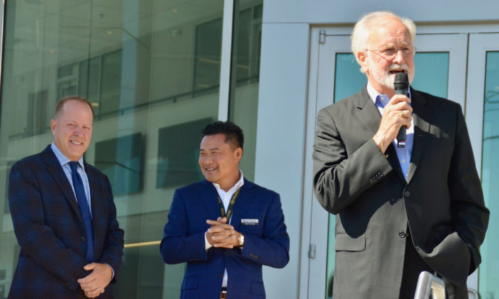 Edmonds Mayor Dave Earling, far right, speaks as Magic Toyota President David Broadus and General Manager Peter Chung look on