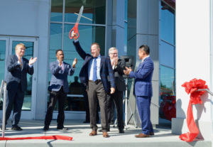 Toyota executives applaud after Magic Toyota President David Broadus cuts the ribbon for the remodeled facility.