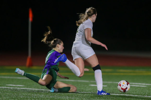 Shorecrest's Sydney VanNess commits a foul against Ingrid Fosberg in the goal box to give Edmonds-Woodway a penalty kick